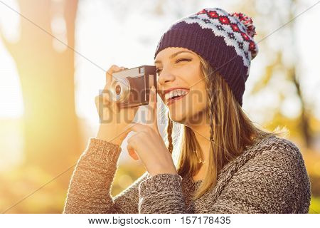Beautiful happy young blonde modern female photographer in park on sunny autumn day, taking a photo using analogue camera. Retouched, vibrant colors, natural lighting.
