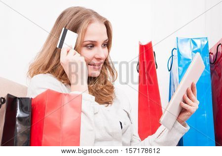 Lady Thinking And Shopping Online Holding Card With Bags Around