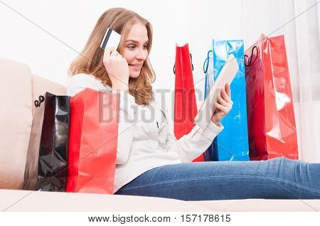 Woman Thinking And Shopping Online Holding Card With Bags Around
