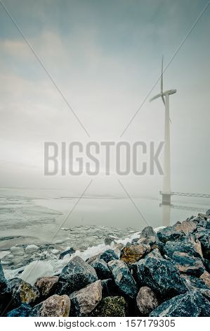 modern white wind turbine for generation of renewable electricity in Dutch winter landscape along the IJsselmeer