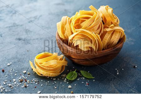 Fettuccine pasta ingredients for Italian food. Pasta tagliatelle with spices and Basil