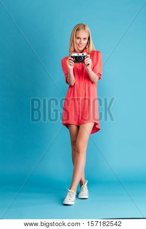 Full length portrait of a young woman photographer in dress standing with retro camera over blue background
