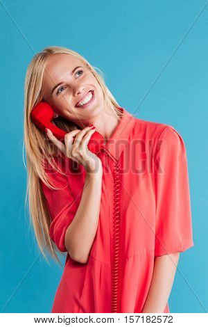 Close up portrait of a cheerful smiling girl in red dress talking on retro telephone isolated on a blue background