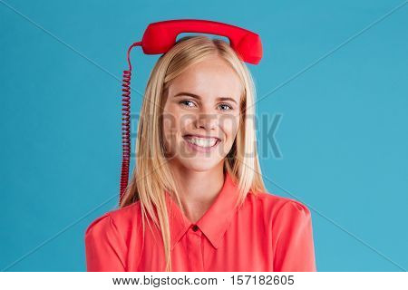 Close up portrait of a smiling happy blonde woman with red tube on her head isolated on a blue background