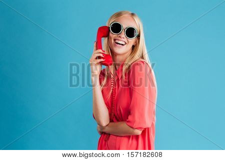 Happy stylish blonde woman talking on red phone and looking at camera isolated on a blue background