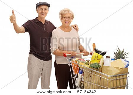 Elderly man giving a thumb up and an elderly woman with a shopping cart full of groceries isolated on white background