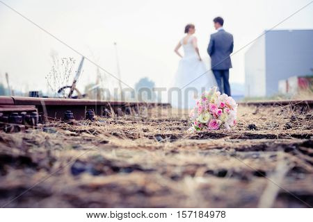 Happy newlywed romantic couple walking on rails on old track.