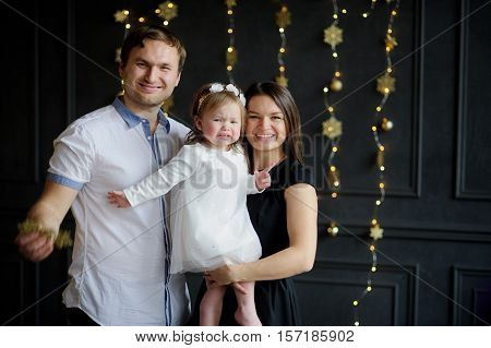 Young parents calm the crying child. The room is festively decorated. Little girl cries on hands at mother. Baby is dressed in a white dress on the head of her a wreath. Parents look in the camera and smile.
