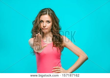 The portrait of disgusted woman showing NO by hand on blue background