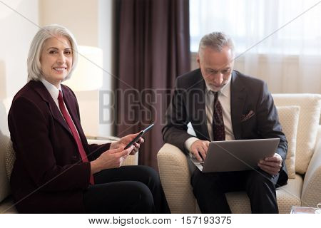 Delighted from work. Cheerful delighted aged businesswoman smiling and holding the tablet while sitting in the office near the colleague with the laptop and working on the project together