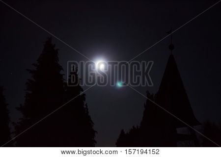 A eerie scene with pale moonlight and silhouettes