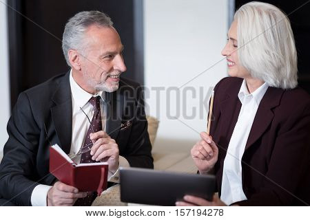 Happy working hours. Smiling delighted pleasant businesswoman sitting in the office near the businessman while working with the tablet and exchanging ideas