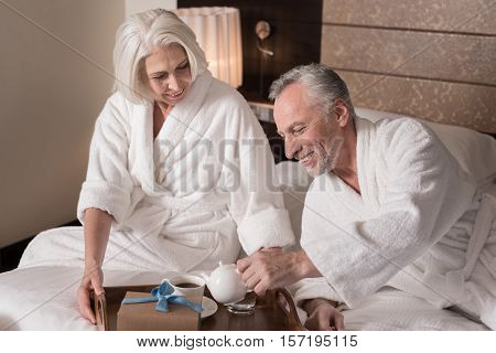 Having breakfast together. Cheerful smiling aged couple lying on the bed and having a breakfast while expressing joy