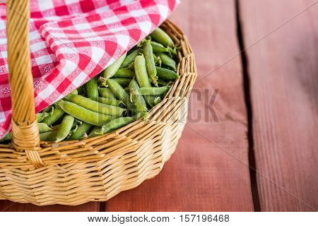 Unopened pea pods in a basket on the wooden background.