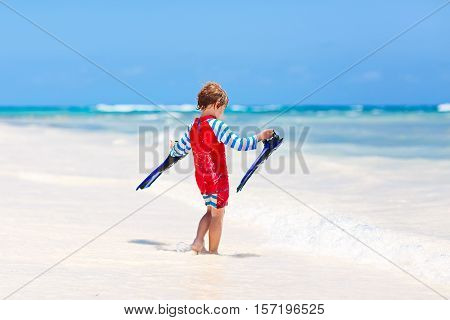 Adorable little blond kid boy having fun on tropical beach of Maldives. Excited child playing and surfing in sun protected swimsuit in ocean on vacations. White sand, Kid holding flippers for swimming