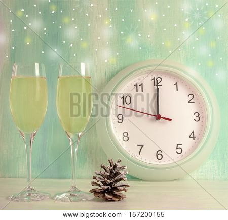 A photo of two flute glasses of sparkling wine with a pine cone, a clock about to strike midnight, snowflakes, and copyspace