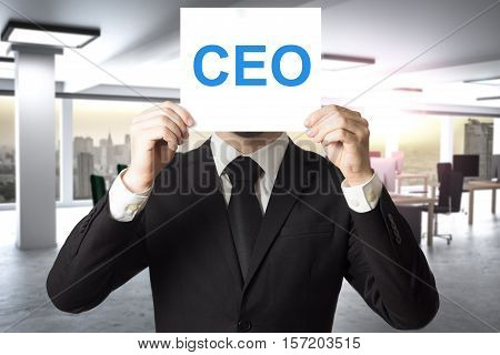 businessman in office hiding face behing sign ceo