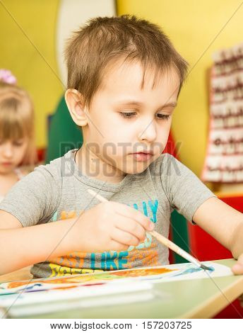 Funny Children Draw Paints And Pencils Brightest Picture In Kindergarten - Russia, Moscow - February