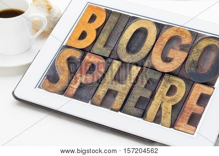 blogosphere (global blog community) word abstract in vintage letterpress wood type on a digital tablet with a cup of coffee