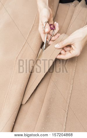 hands cutting cloth. Dressmaker prepares wrap detail with sketch lines.