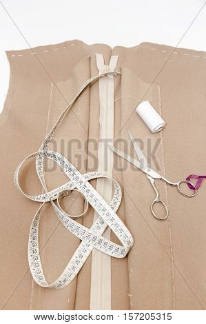 Cloth, scissors, meter and zipper. Dressmaker prepares wrap detail with sketch lines.