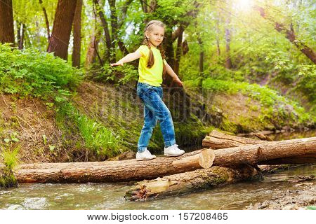 Portrait of cute girl balancing on a log bridge, crossing the river in summer forest