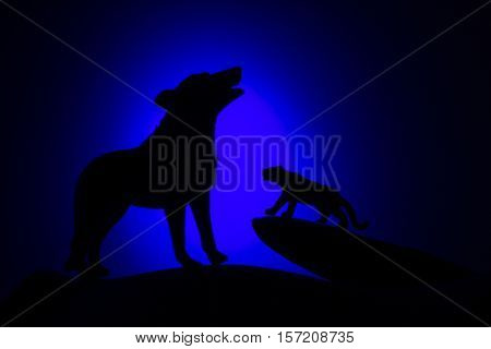 wolf in silhouette howling to the full moon.