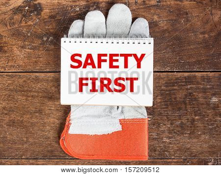 White card in safety glove with the inscription SAFETY FIRST on wooden background