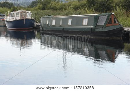 Boats moored along a canal towpath in the countryside
