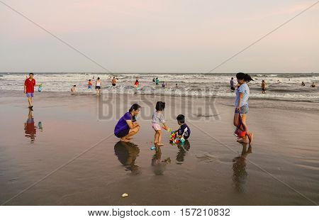People Relax On The Beach At Sunset