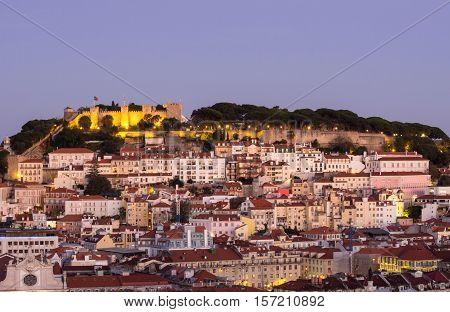 Cityscape of Lisbon Portugal with the Sao Jorge Castle seen from Miradouro Sao Pedro de Alcantara at night.