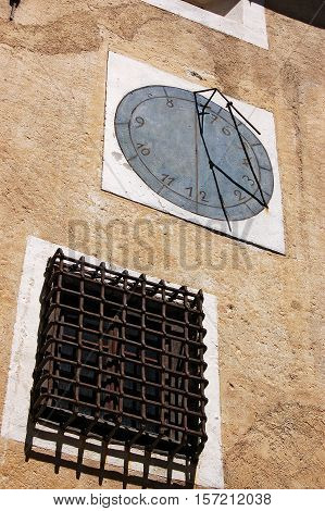 Old sundial on a wall with ancient window. Engadine Switzerland Europe