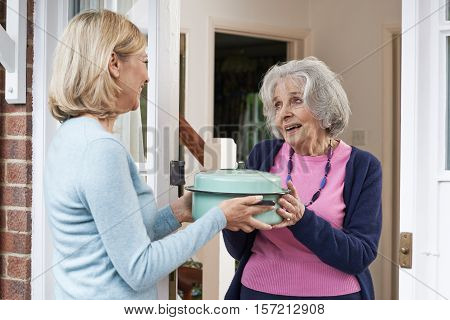 Mature Woman Bringing Meal For Elderly Neighbour