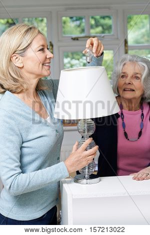 Female Neighbor Helping Senior Woman Change Lightbulb In Lamp