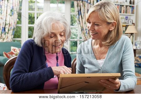 Senior Woman Looks At Photo In Frame With Mature Female Neighbor