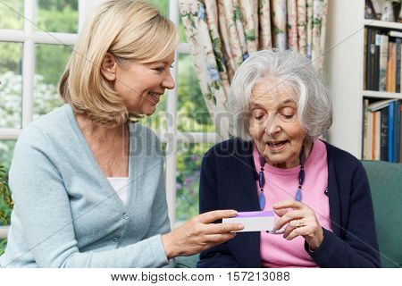 Female Neighbor Helping Senior Woman With Medication
