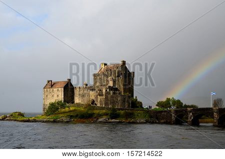 Eilean Donan castle with a rainbow lighting up the landscape.
