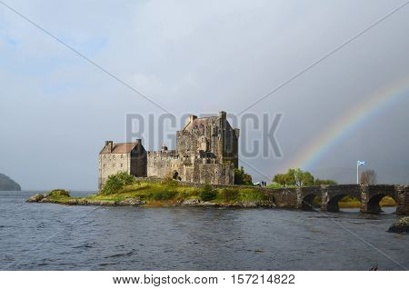 Eilean Donan Castle after a storm with a rainbow remaining.