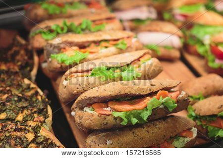 Beautifully decorated catering banquet table with different toasted triangle sandwiches on a plate on corporate christmas birthday party event or wedding celebration