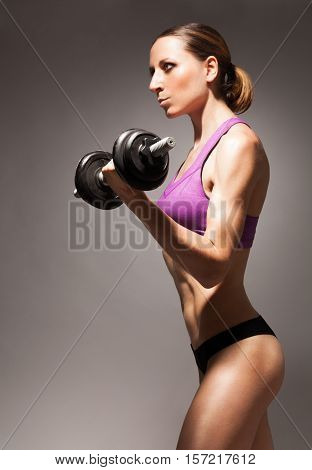 Strong fit young woman exercising with dumbbell side view dramatic portrait