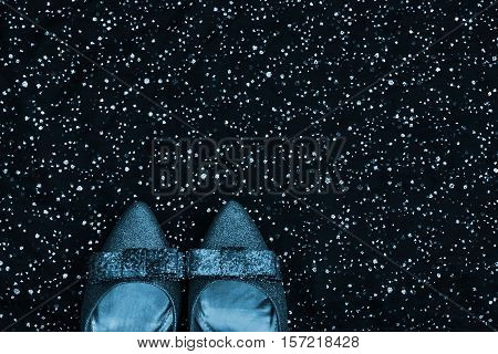 Copy space. Isolated glittery shoes on a black sparkling background