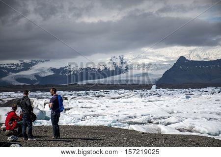 Iceland men standing at glacier lake Jokulsarlon glacial lagoon nature with snow landscape Vatnajokull 2