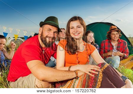 Close-up portrait of happy couple in love sitting on the grass among their friends at campsite on open air festival