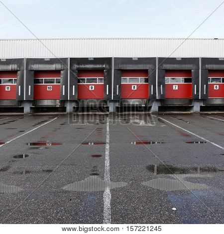 numbers 6 to 11 on red doors of loading docks behind rain puddles on tarmac