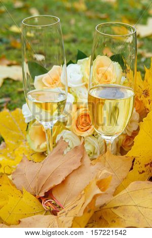 Autumn etude with champagne glasses in yellow maple leaves. Still life in the Park. Rest and celebration of nature in autumn.