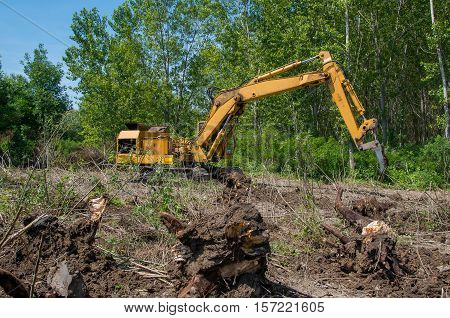Removing stumps with an excavator. Mechanical Site Preparation for Forestry.