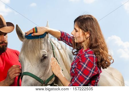 Close-up portrait of young woman brushing beautiful white horse while man in cowboy hat holding it by a bridle