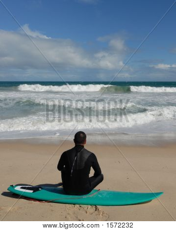 Surfer Sits On His Board