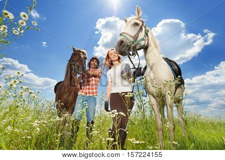 Portrait of happy young couple with purebred horses in flowery meadows at sunny day