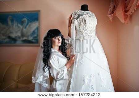 Young Cute Brunette Bride Looking At Her Wedding Dress On Mannequin.